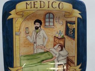 (CODICE ARTICOLO: PMM/04) Piatto quadrato in ceramica, dipinto a mano con rappresentazione del mestiere: Il medico. Tecnica:maiolica
