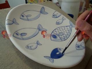 """Decorazione di un piatto in maiolica con decoro dei """"pesci blu""""."""