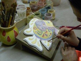 Decorazione a mano con colori soprasmalto di un pesce da parete.