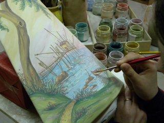 Decorazione a mano con colori soprasmalto di una tegola realizzata su misura, raffigurante il trabocco.
