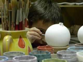 Piccolo artista dipinge la sua pallina in ceramica