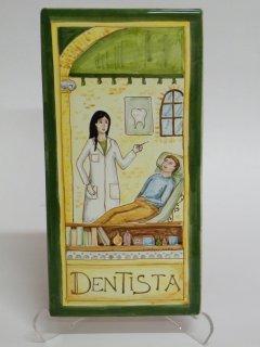 (CODICE ARTICOLO: MM/09) Mattonella fatta e dipinta a mano con rappresentazione del mestiere: La dentista Tecnica:maiolica