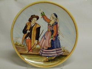 (CODICE ARTICOLO: LC/07): Piatto in ceramica dipinto a mano raffigurante costumi tradizionali di Scanno. Tecnica: maiolica.