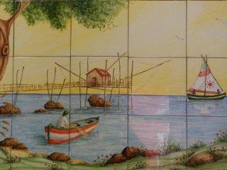 (CODICE ARTICOLO: HI/14) Pannello in ceramica dipinto a mano di cm. 60x100 con trabocco, pescatore e barca a vela. Tecnica: maiolica.